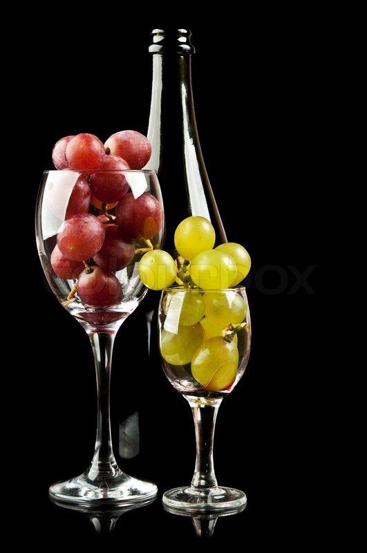 Trauben in ein Glas und eine Flasche Wein auf Stock-Foto