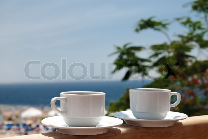 White Cup Of Coffee Near Sea Beach And Pools Stock Photo