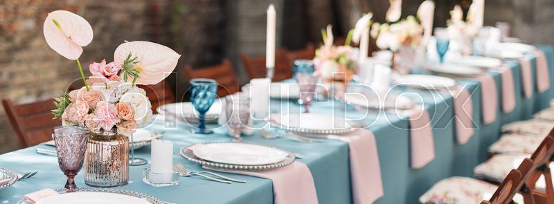 Flower table decorations for holidays and wedding dinner. Table set for holiday, event, party or wedding reception in outdoor restaurant. Banner for website, stock photo