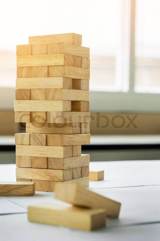The blocks wood tower game with architectural engineer plans or blue prints compasses ,pencils and ruler on wooden table, plan and building concept, stock photo