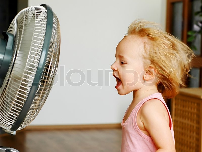 People Using Electric Fan : A little girl standing in front of fan stock photo