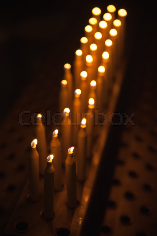 Burning prayer candles stand in a row dark Catholic church interior vertical photo | Stock Photo | Colourbox & Burning prayer candles stand in a row dark Catholic church interior ...