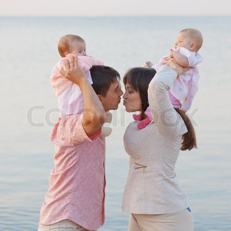 Stock image of 'Young parents with children kissing over sea'