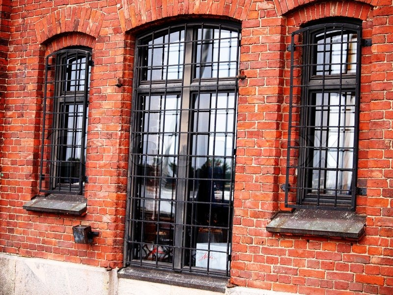 Old Red Brick Building With Steel Fence Stock Photo