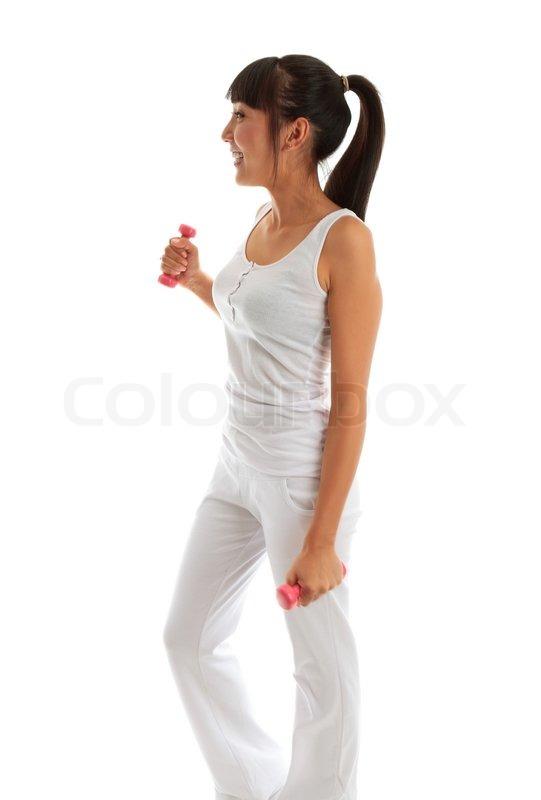 Smuk ung og glad pige træning med håndvægte til at opbygge muskler, fast og tone Hun er iført ...