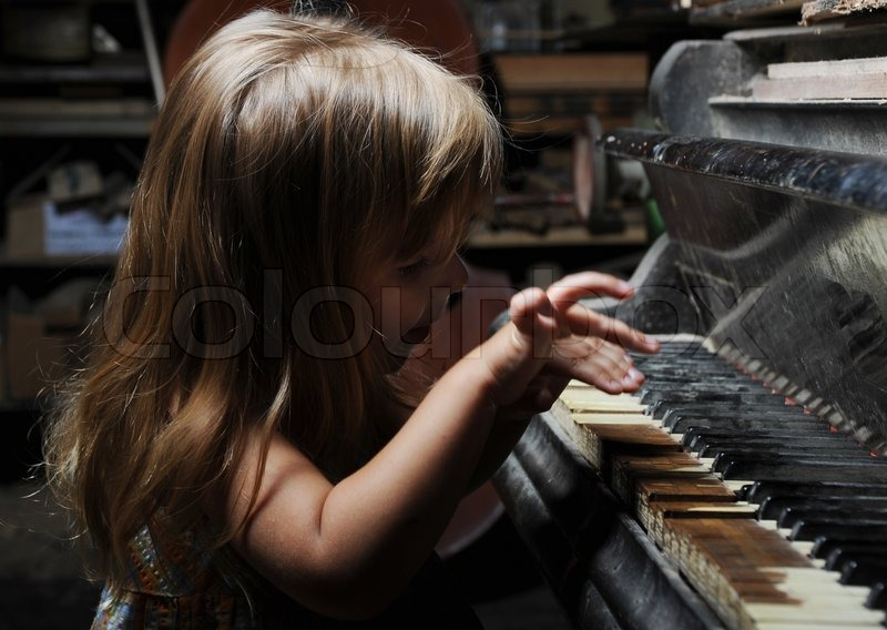 Funny girl playing on an old black     | Stock image | Colourbox