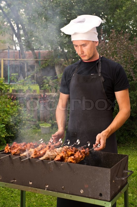 Man Cook Grilling Meat On Coal In Brazier Stock Photo