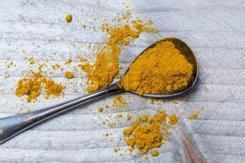 Curry powder on a spoon macro, stock photo