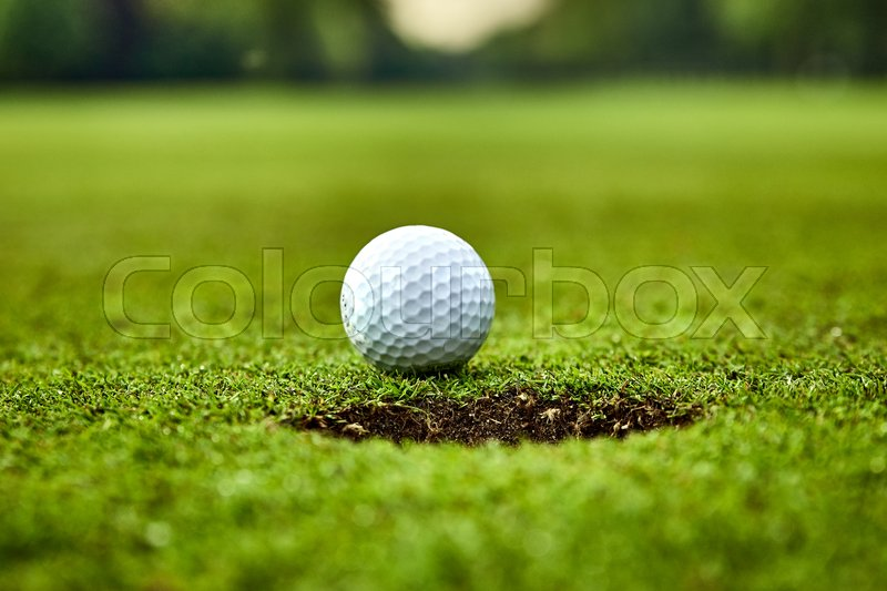Golf ball on the green. golf ball on lip of cup, stock photo