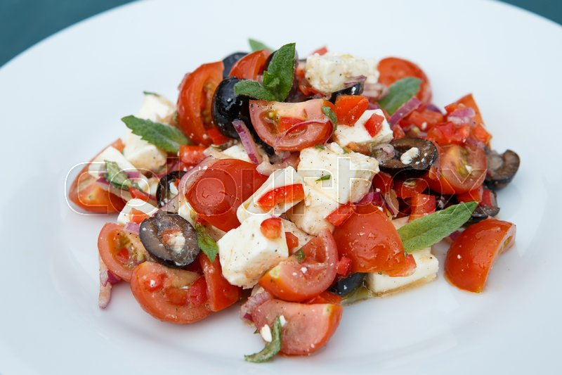 Stock image of 'Vegetable salad with feta cheese on white plate'