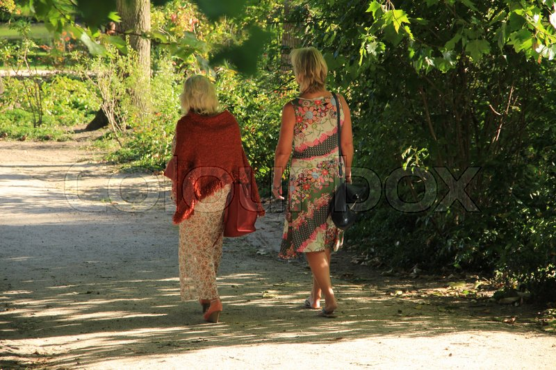 The two ladies discuter their problems in the shadow of the trees in the urban park in the summer, stock photo