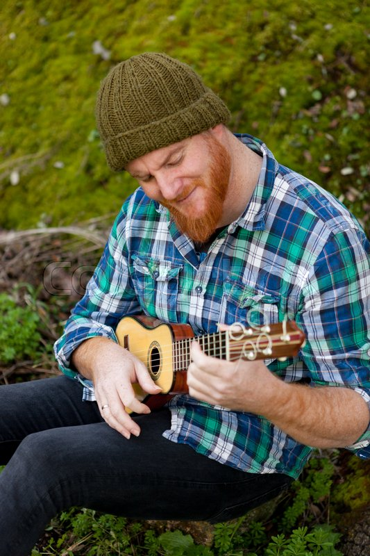 Hipster man with red beard playing a ukulele in the field, stock photo