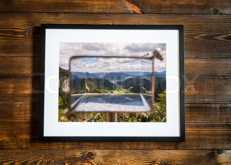 Beautiful landscape photo in frame on wooden desk, stock photo