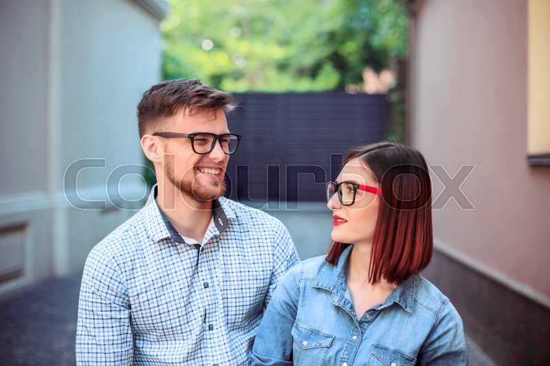 Happy funny couple standing outdoors at street of city and laughing on the bright sunny day and green summer background, stock photo