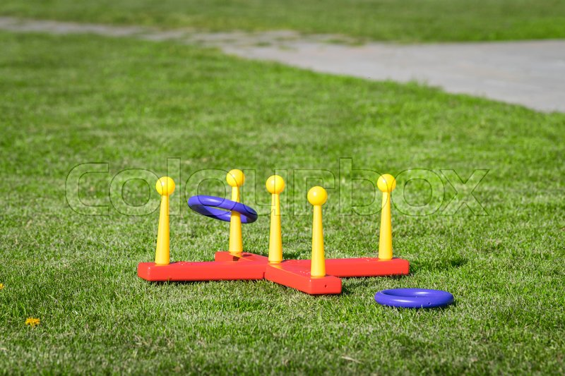 Ring throw summer game on a green lawn in the sun made of plastic, stock photo
