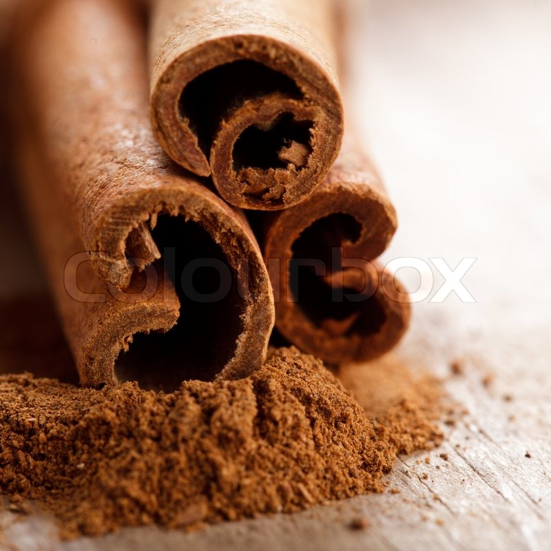 Cinnamon sticks and meal close up on wooden table stock