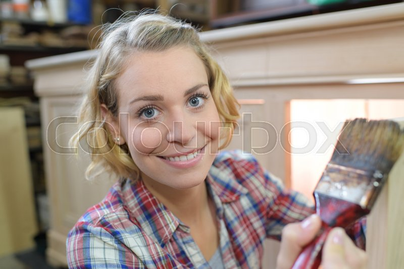 Portrait of woman painting a cupboard, stock photo