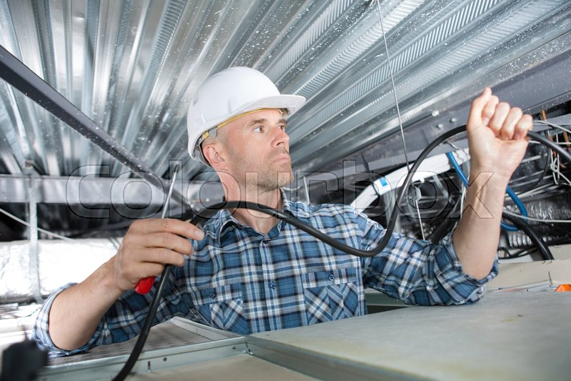 Electrician installing cables in roof, stock photo
