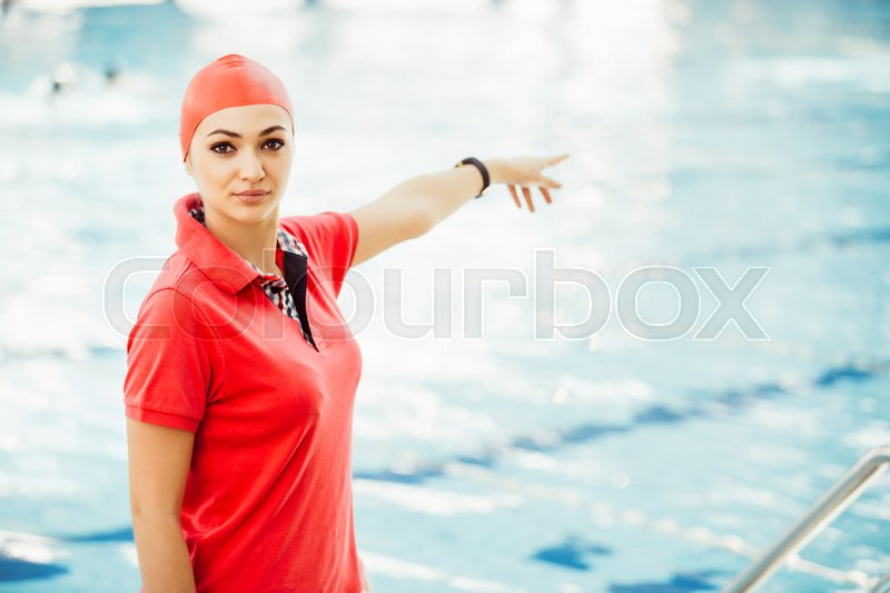 Portrait of female coach with a stop watch and clipboard by pool at leisure center, stock photo