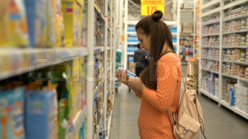 Stock image of 'Young mom buys baby food in supermarket.'