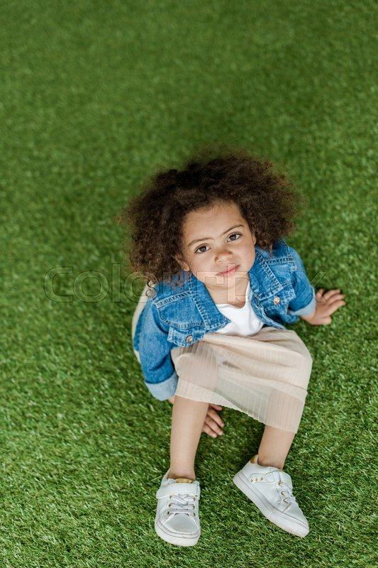 Cute african american curly girl resting on lawn, stock photo