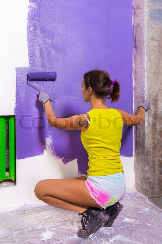 Young attractive woman paints white wall and purple paint roller, stock photo