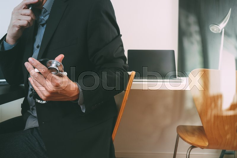 Smart medical doctor working with smart phone and digital tablet and laptop computer and stethoscope in modern office at hospital, stock photo