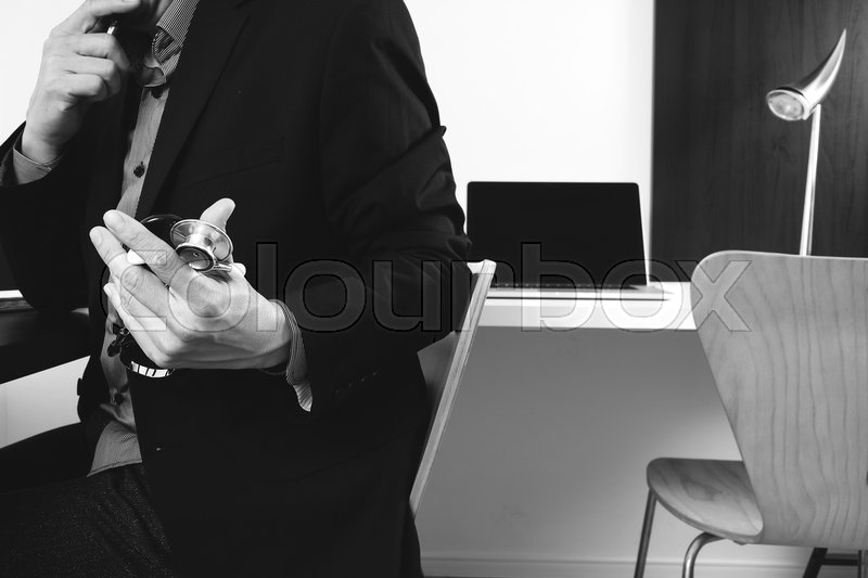 Smart medical doctor working with smart phone and digital tablet and laptop computer and stethoscope in modern office at hospital,black and white, stock photo