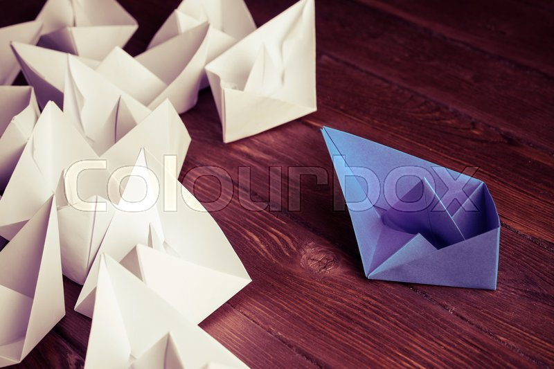 Business leadership concept with white and color paper boats on, stock photo