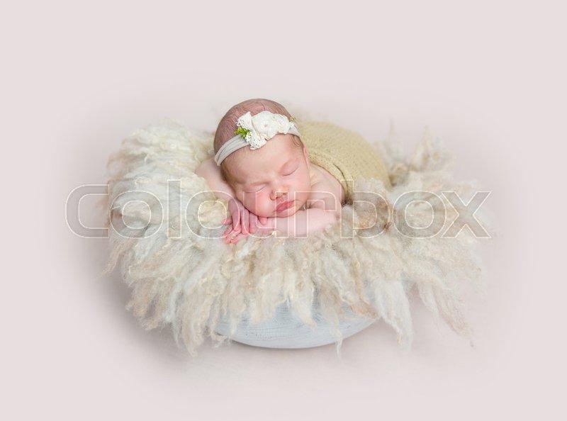 Adorable girl sleeping on huge soft fury pillow, wearing cute little headband, stock photo