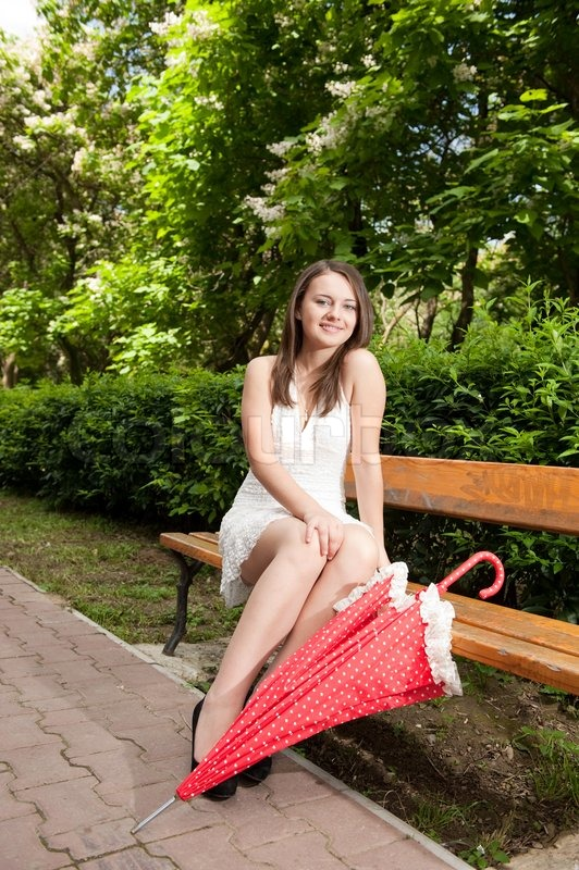 young girl sitting on bench with umbrella stock photo