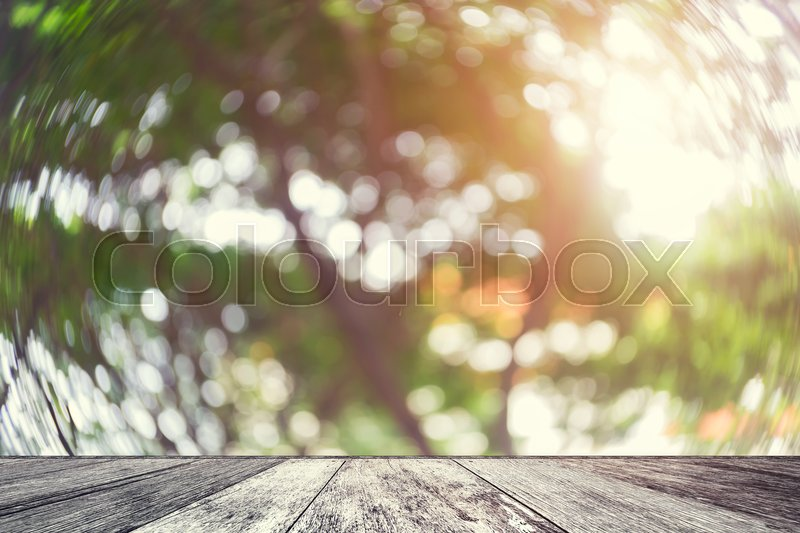 Wood table with blurred nature background. Abstract blurred tree with sunlight and wood shelf product display.Empty perspective wood table and space with green nature blur background.Vintage filtered, stock photo