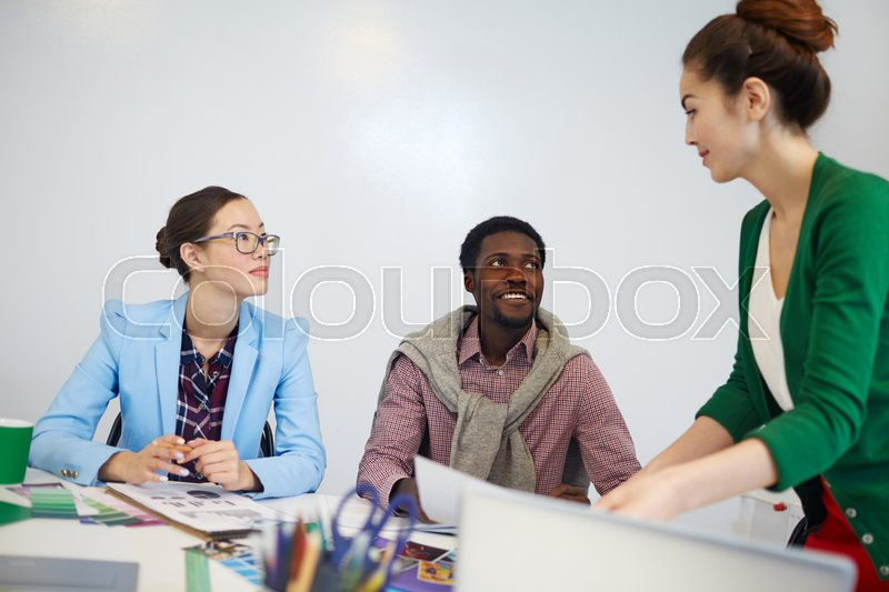 Two managers listening to their leaer while discussing ideas, stock photo