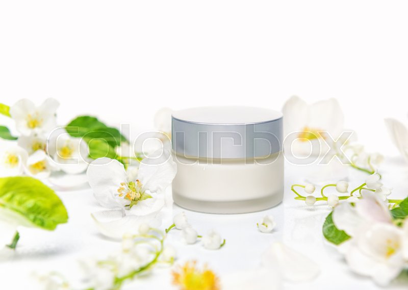 Mockup of hand, facial or body cream cosmetic bottles with spring flowers, concept announcement sale or promotion new product, stock photo