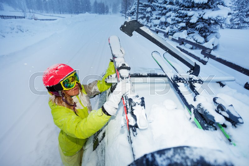 e2a4c8c9340f Stock image of  Top view portrait of female skier fastening skis to roof  rails of