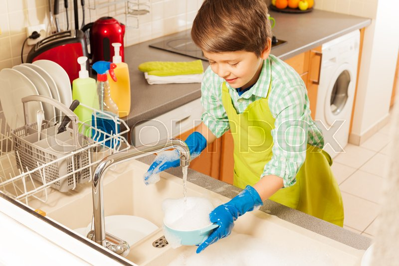 little child boy cleaning and washing dishes in the kitchen sink under water from tap stock. Black Bedroom Furniture Sets. Home Design Ideas