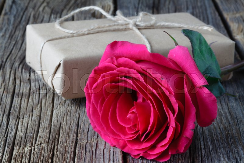 Single fresh pink rose symbolic of love and romance on a rustic wooden table for a sweetheart on Valentines Day, Mothers Day or anniversary, stock photo