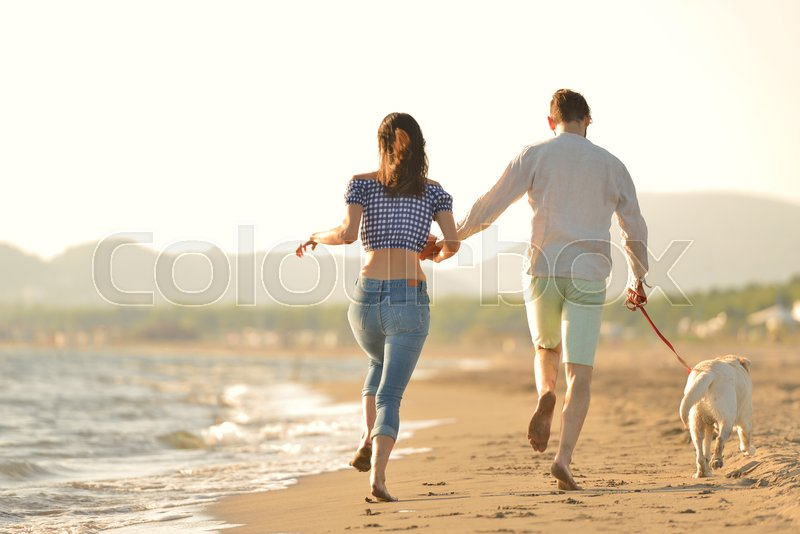Two young people running on the beach kissing and holding tight with dog, stock photo
