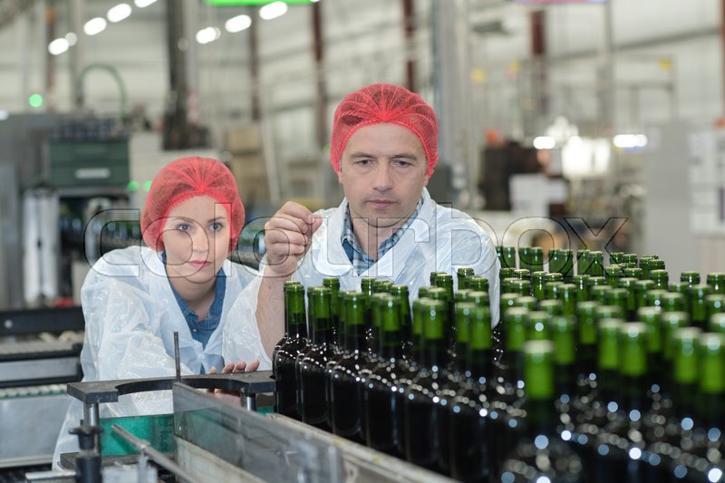 Workers examining wine bottles at bottling plant, stock photo