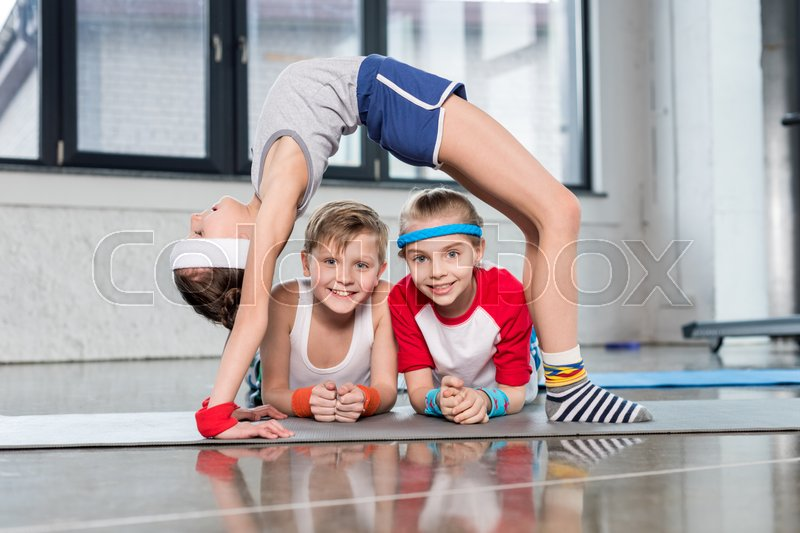 Cute sporty kids exercising in gym and smiling at camera, children sport school concept, stock photo