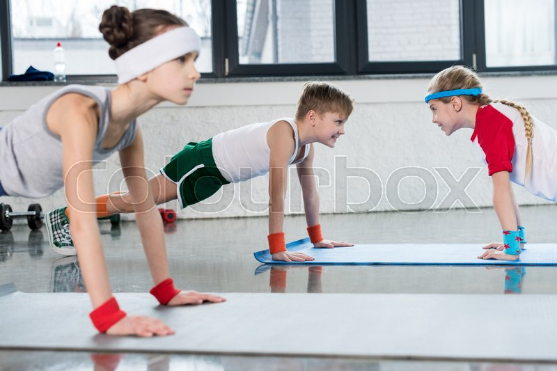 Cute sporty kids exercising on yoga mats in gym and smiling, children sport school concept, stock photo