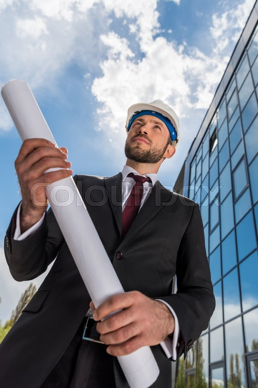 Low angle view of professional architect in hard hat holding blueprint and looking away, stock photo