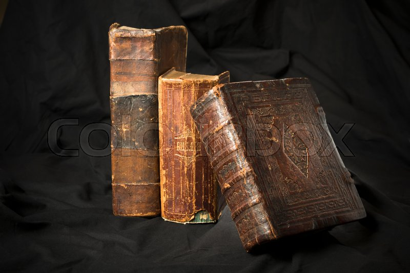 Old book spines on black background. Ancient library. Antique Holy Scripture books. Antique books collection. Wisdom knowledge in old books. Torn hard cover books spine sides, stock photo