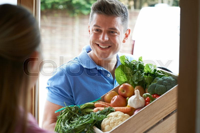 Man Making Home Delivery Of Organic Vegetable Box, stock photo