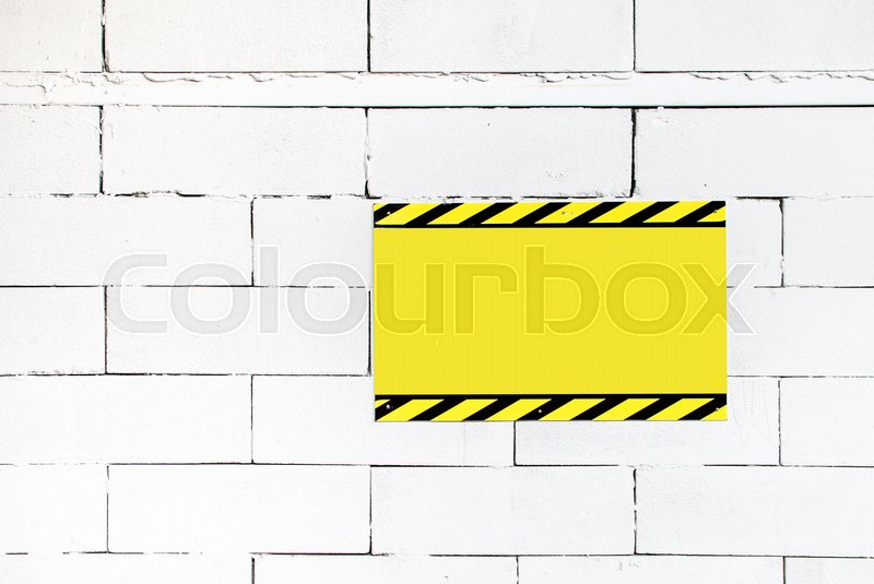 Cement block wall with blank warning poster,template to fill your text, stock photo