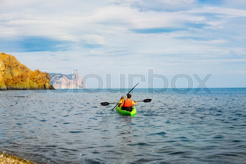 Family on kayaks and canoe tour. Father and child paddling in kayak in a river on a sunny day. Children in summer sport camp. Active preschooler kayaking in a lake. Water fun during school vacation, stock photo