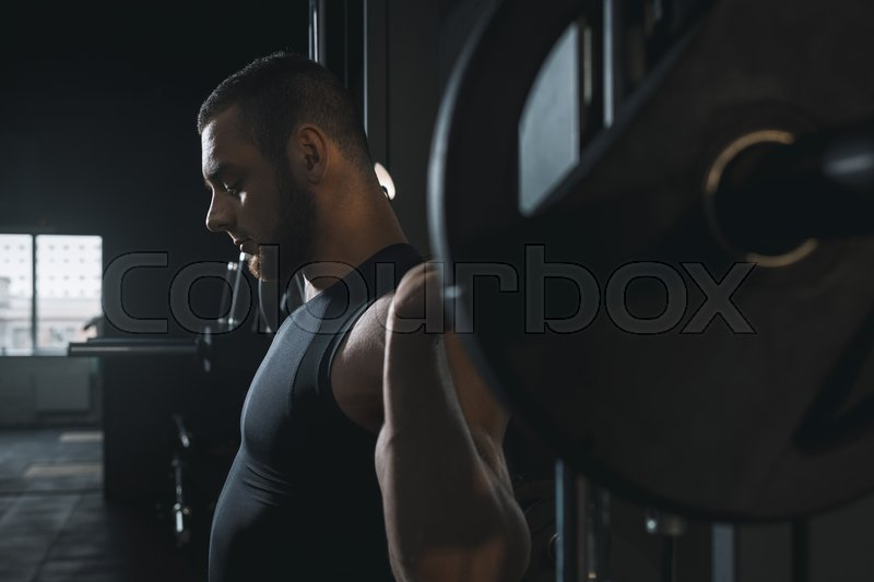 Concentrated muscular sportsman training with barbell in sports center, stock photo