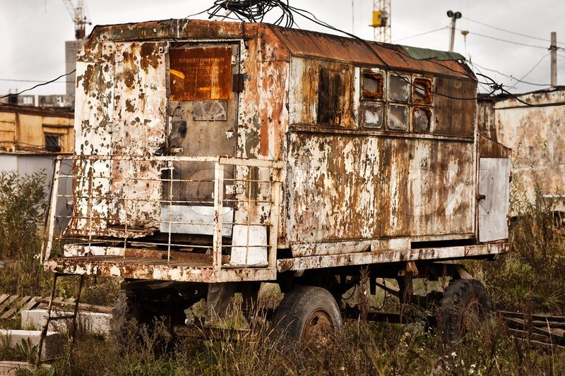 Old Rusty Wagon Wheel Vehicle On Industrial Building
