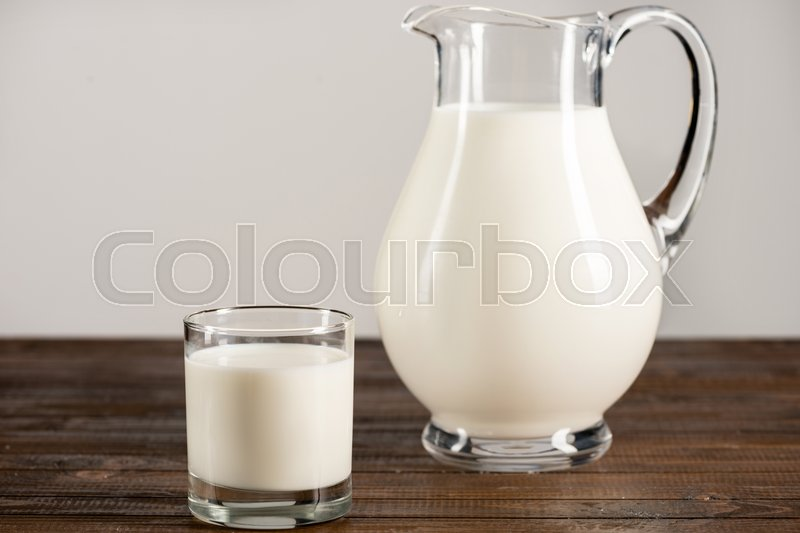 Close-up view of fresh organic milk in glass jug and glass on wooden table top, stock photo
