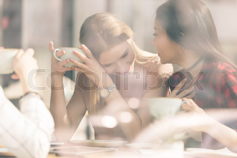 Friends spend time together on coffee break in cafe, stock photo